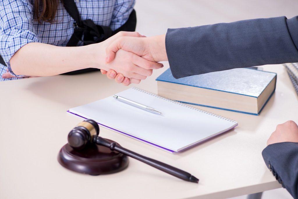 Injured client shaking hands with her lawyer