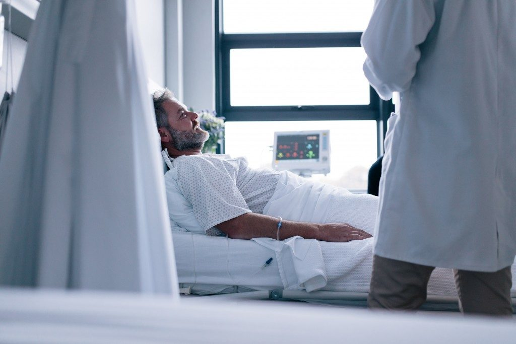man in hospital bed smiling at his doctor