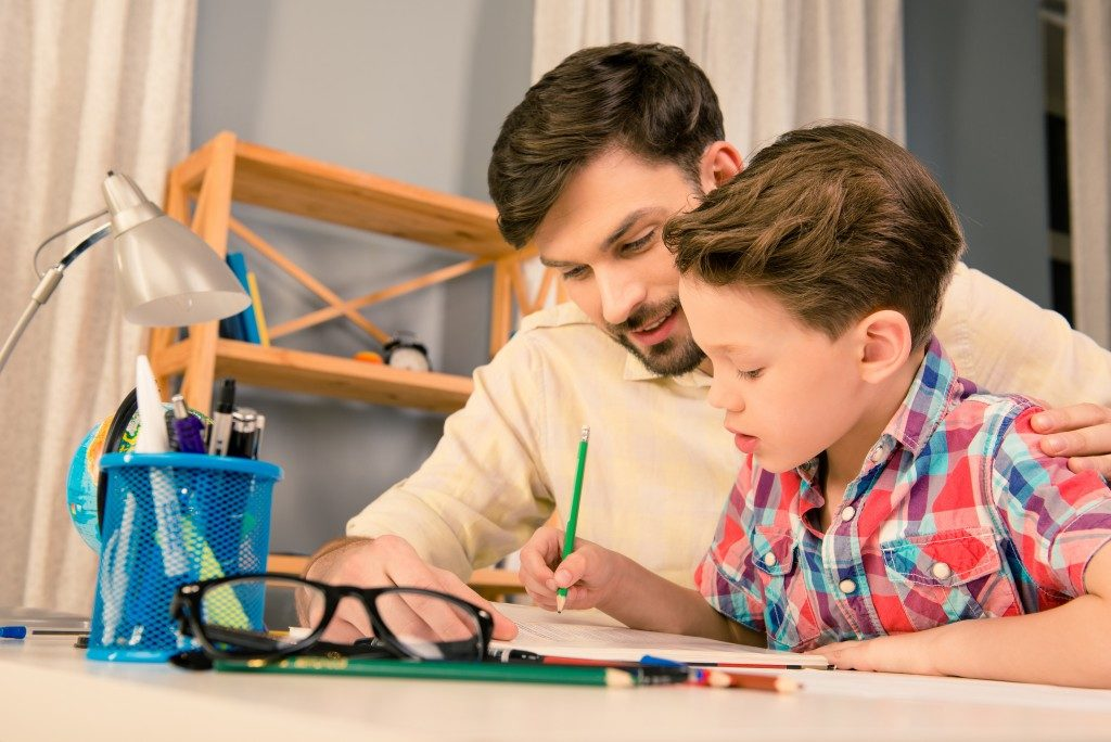 Dad encouraging his son in writing