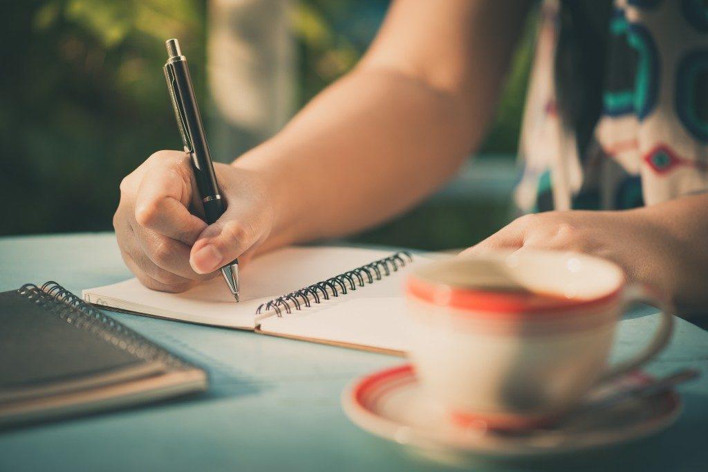 Woman hand writing on journal