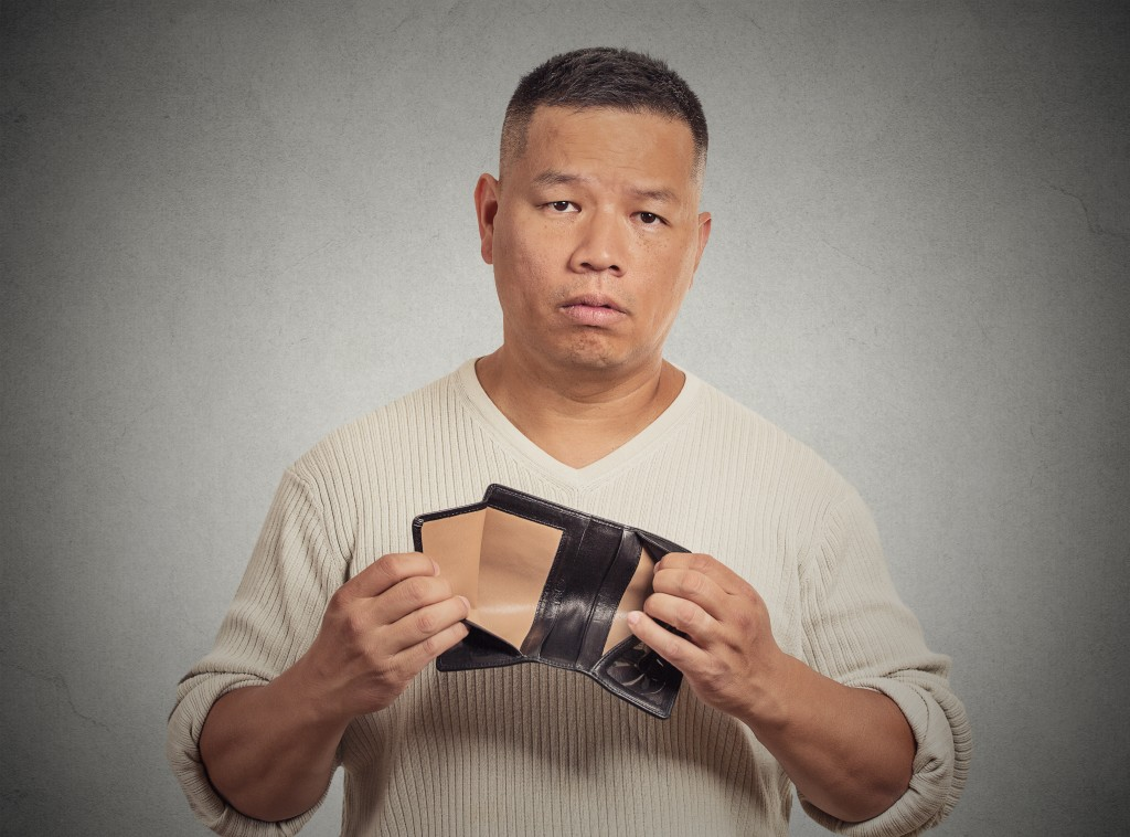 man holding out empty wallet